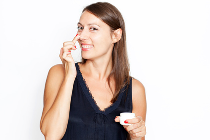Woman applying lotion on her nose